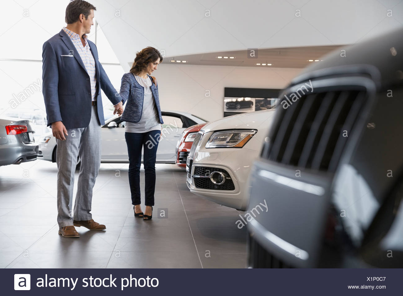 Couple shopping in car dealership showroom - Stock Image