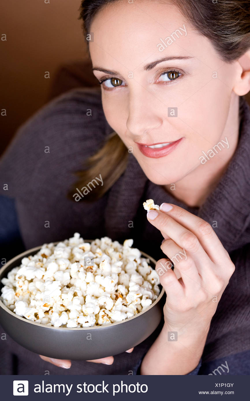 A mid adult woman eating popcorn - Stock Image