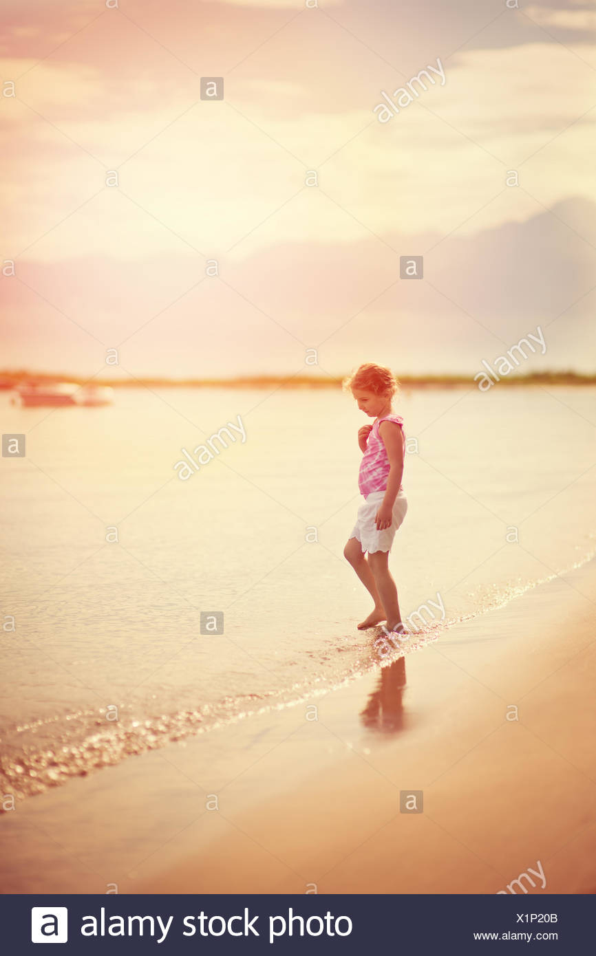 Girl standing on the beach at the water's edge - Stock Image