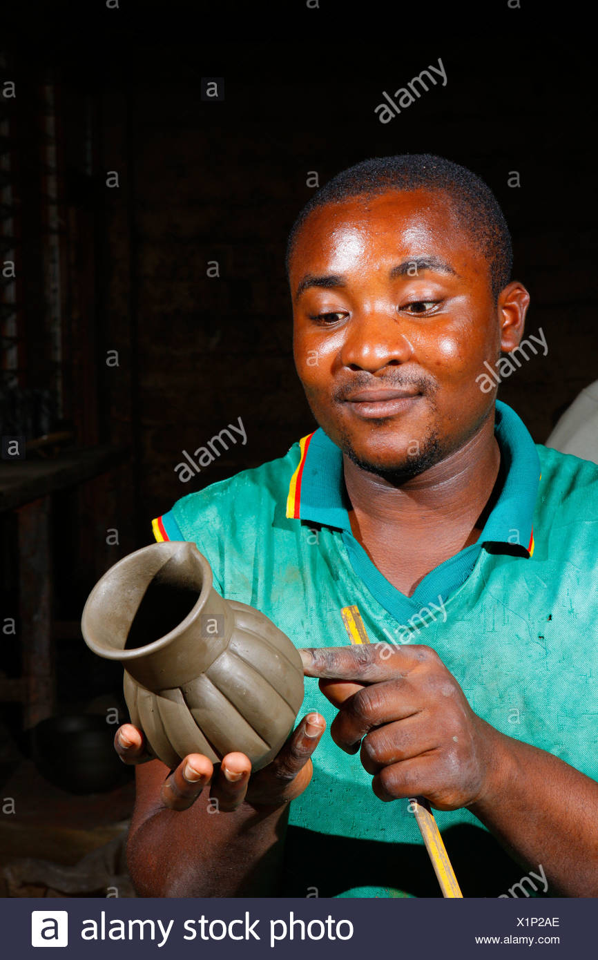 Man working on earthenware vase, production of pottery, Bamessing, Cameroon, Africa - Stock Image