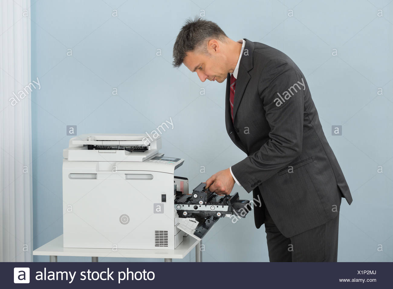 Businessman Fixing Cartridge In Printer Machine At Office - Stock Image