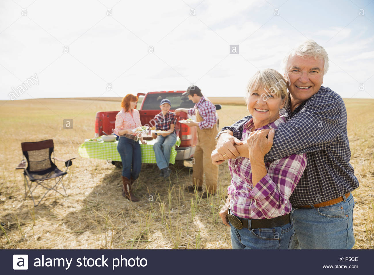 Multi-generation family enjoying lunch in crop field - Stock Image