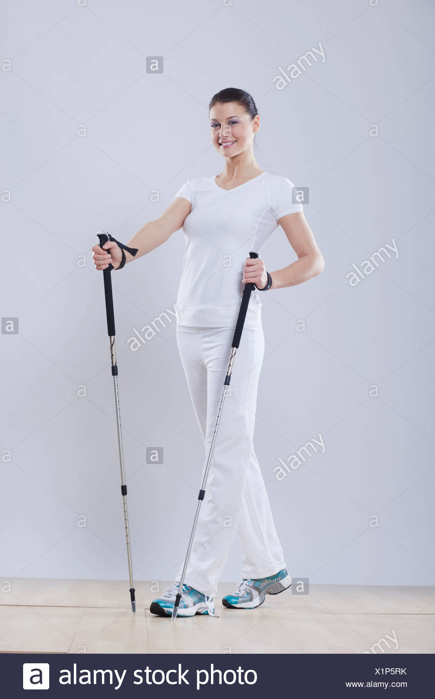 Mid adult woman with ski sticks against white background, smiling, portrait - Stock Image