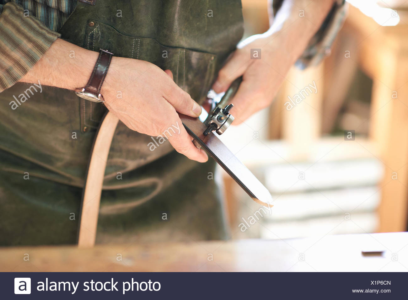 Male worker in leather workshop, punching holes in leather belt, mid section, close-up Stock Photo