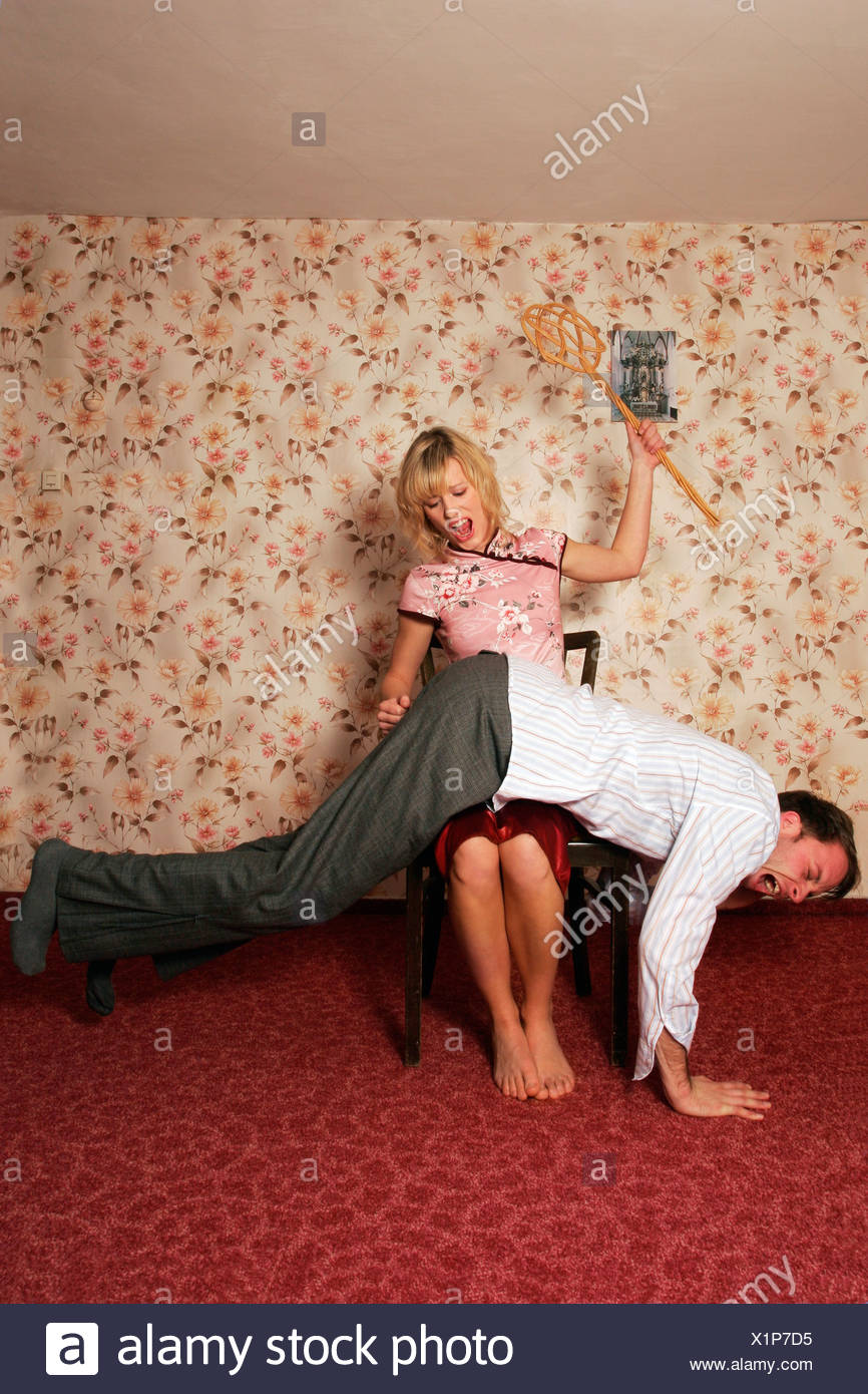 Young woman spanking man - Stock Image