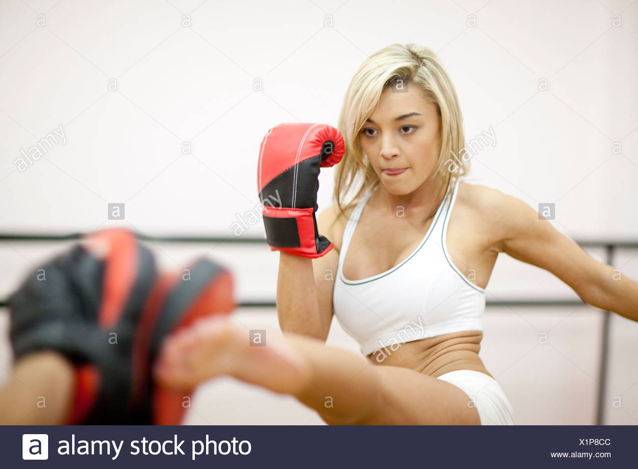 Young woman kickboxing in gym - Stock Image