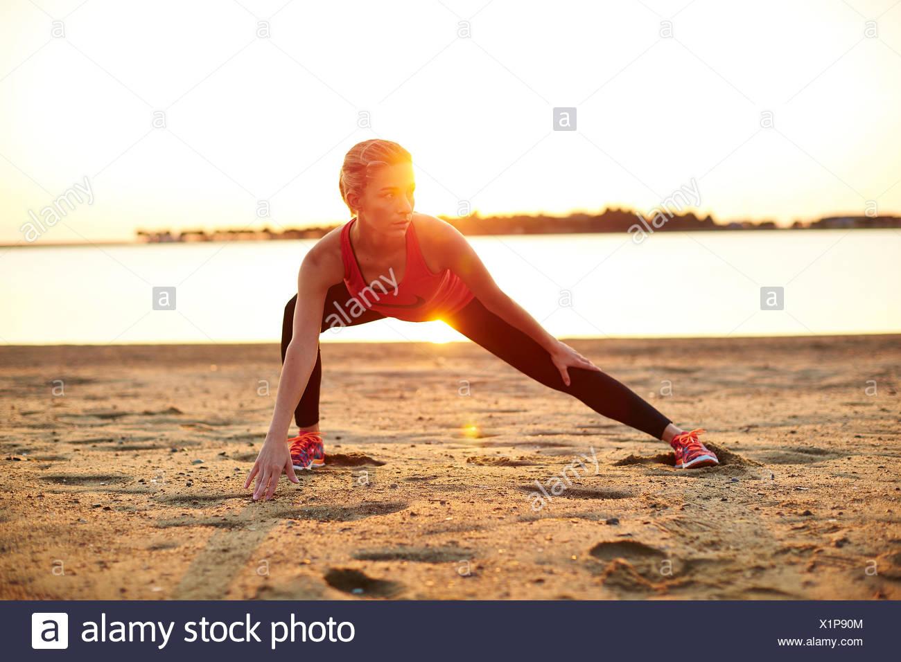 A young athletic woman working out outdoors. - Stock Image