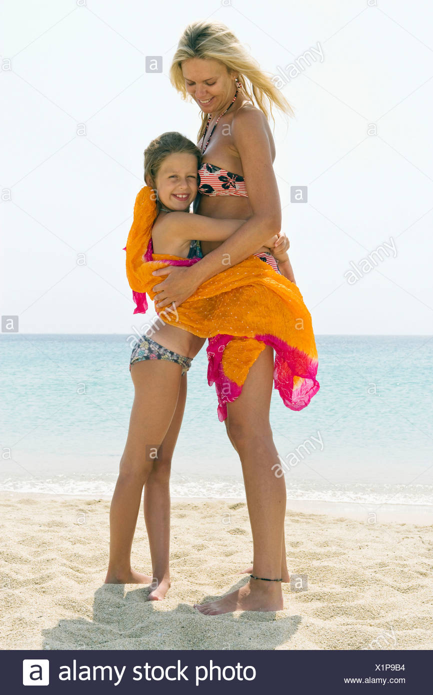 Woman and young girl embracing at the beach smiling. Stock Photo