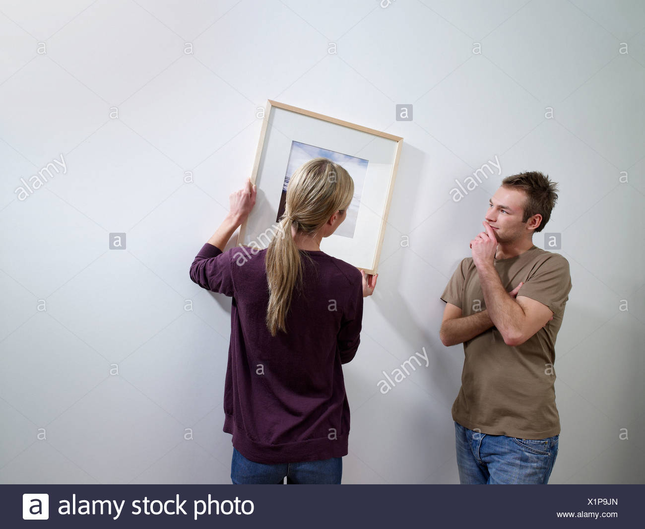 A couple putting art on a wall - Stock Image