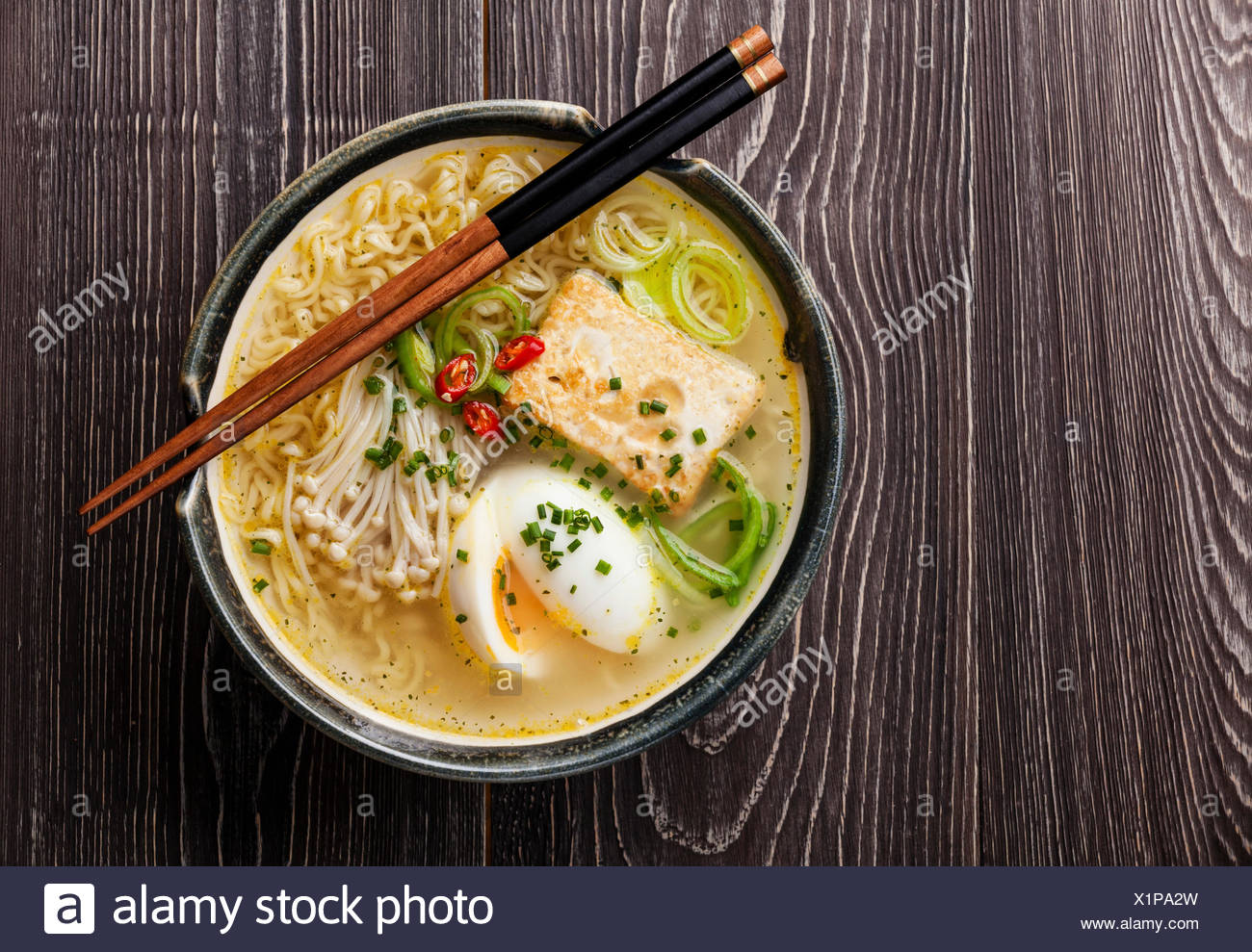 Asian Miso ramen noodles with egg, tofu and enoki in bowl on gray wooden background - Stock Image