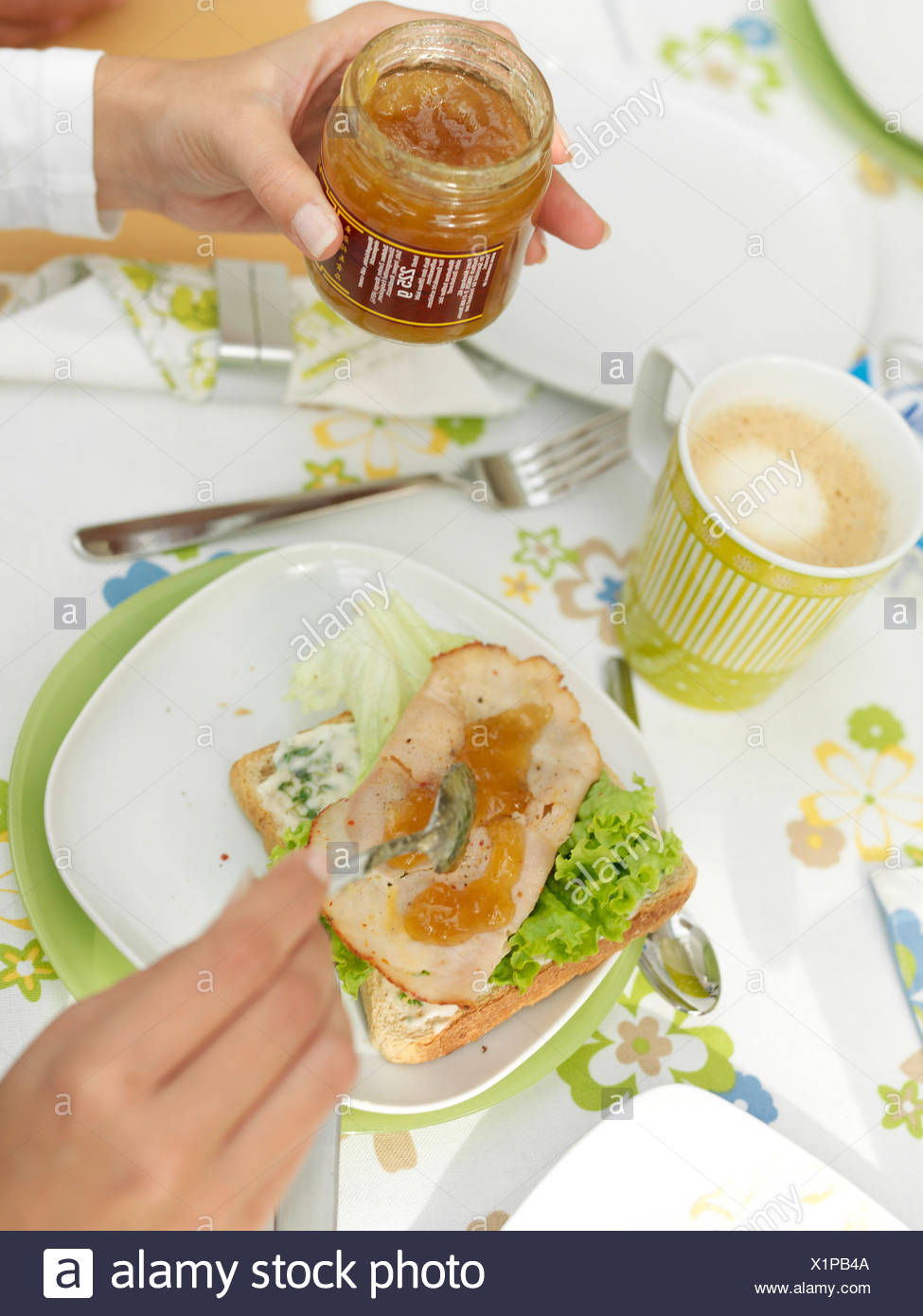 Person's hands spreading jam on prosciutto - Stock Image