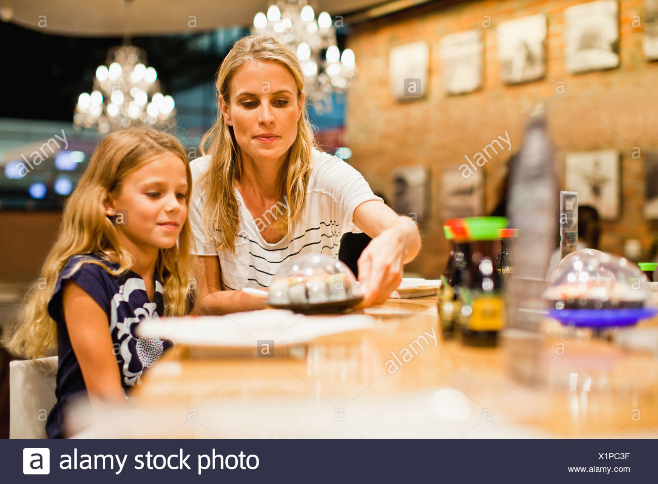 Mother and daughter eating at restaurant - Stock Image