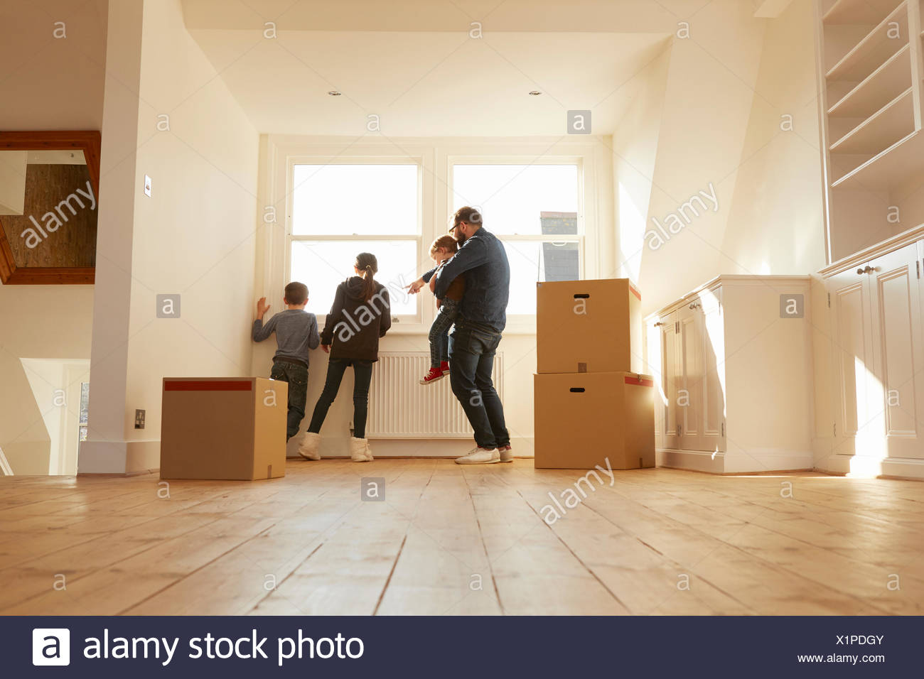 Mid adult man and three children looking from window of new home - Stock Image