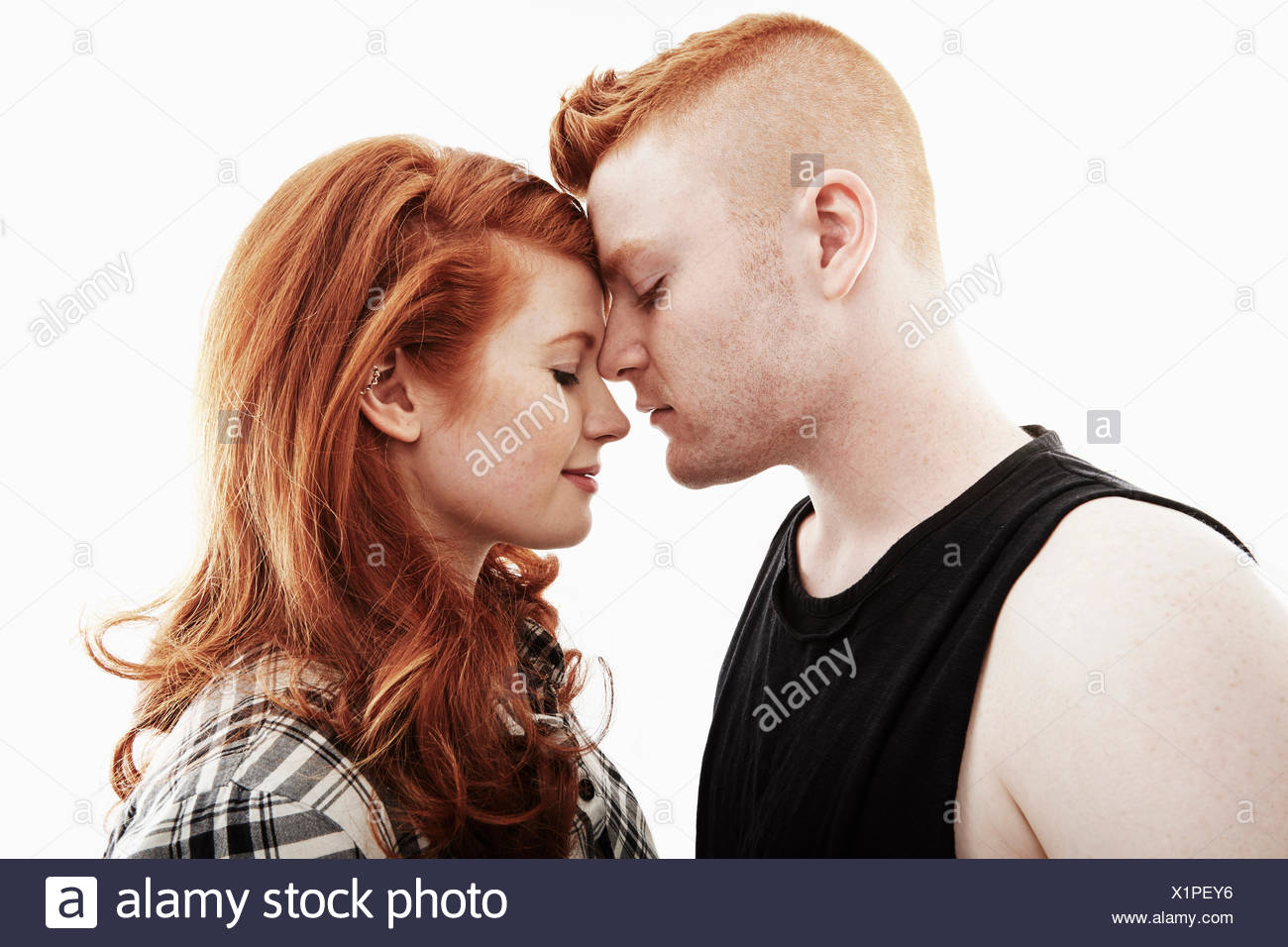 Studio portrait of red haired young couple head to head with eyes closed - Stock Image