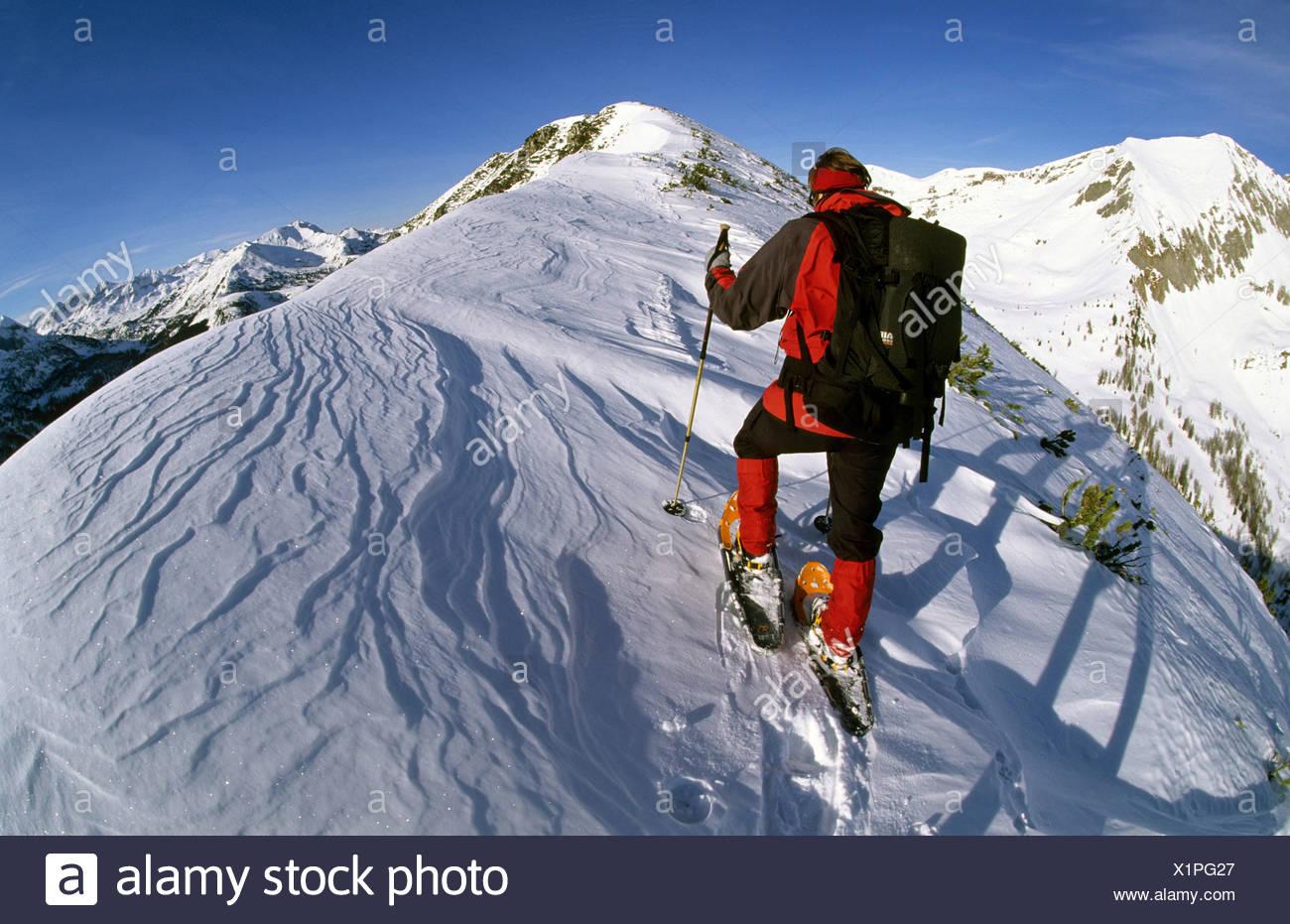 Woman in snowshoes on the summit chine of Mt. Spirzing, 2066m, Suedwiener Hut, Radstaedter Tauern Range, Salzburg, Austria - Stock Image