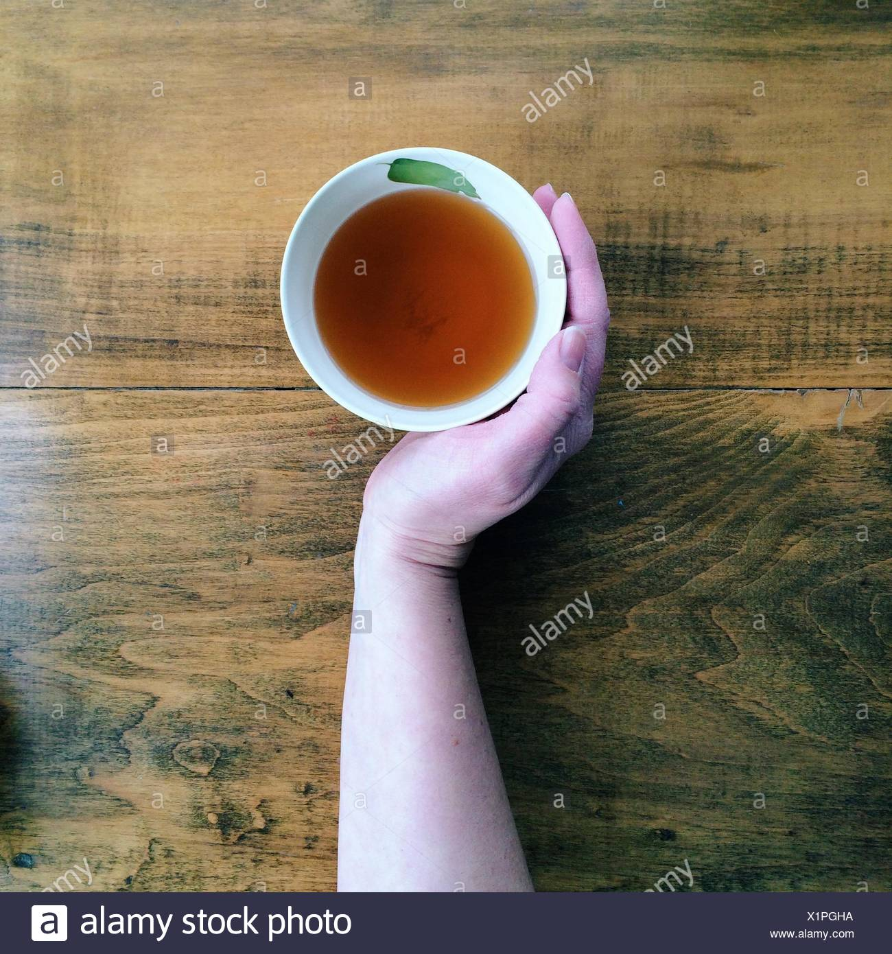 Hand with cup of tea - Stock Image