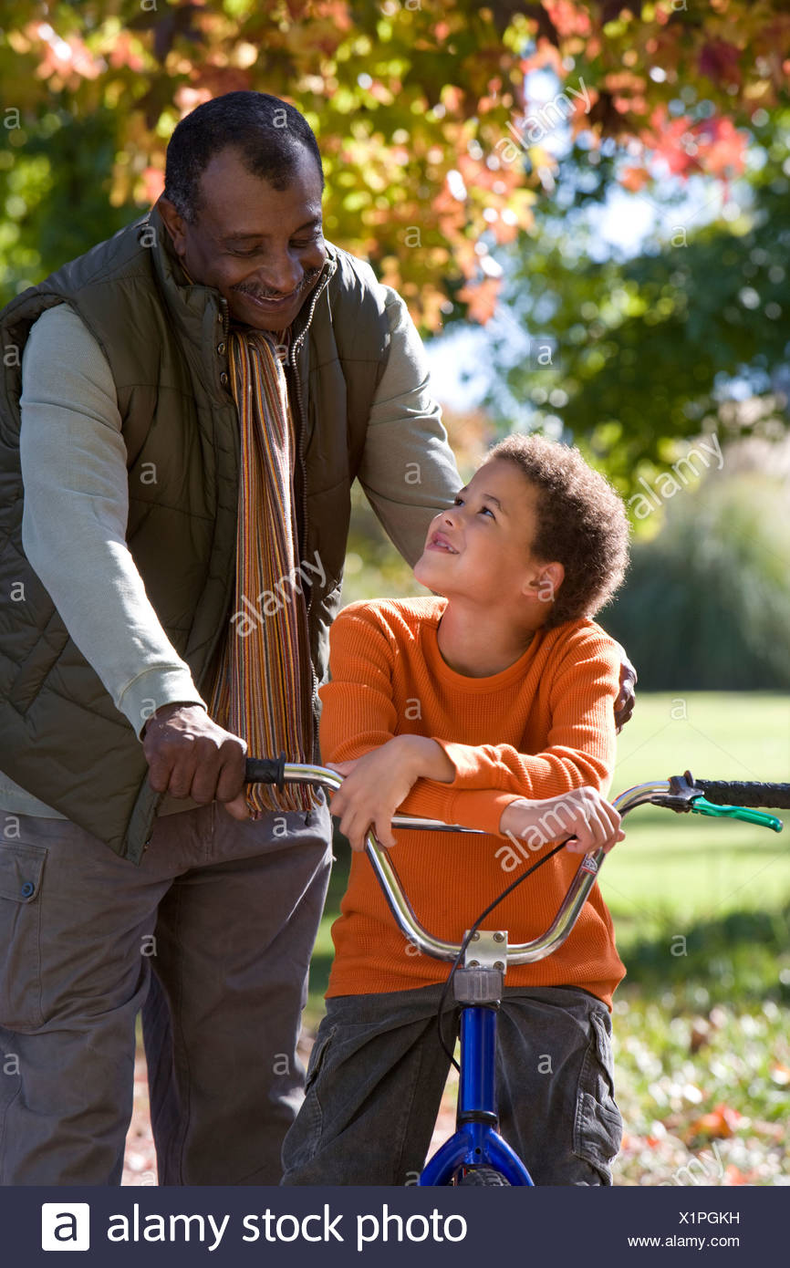 Grandfather helping grandson learn to ride a bicycle - Stock Image