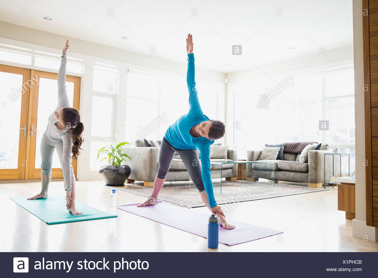 Mother And Daughter Doing Yoga In Living Room