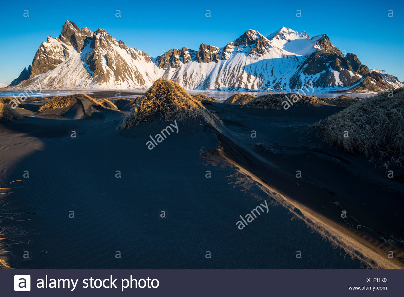 Stokksnes, Eastern Iceland, Europe. Small mounds in with Vestrahorn mountain in the backdrop in a frozen winter landscape. Stock Photo