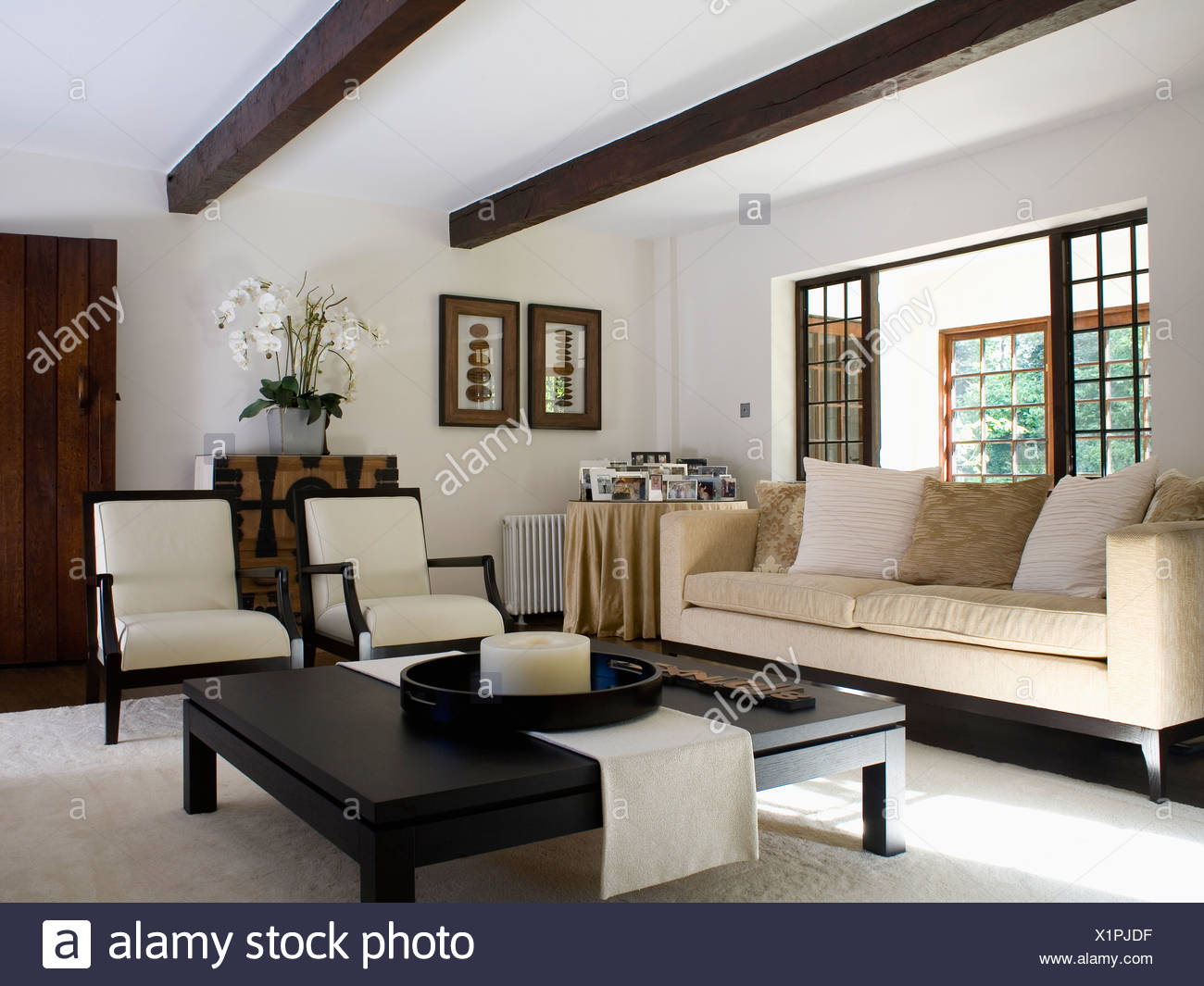 Cream sofa and chairs in modern cottage living room with ...