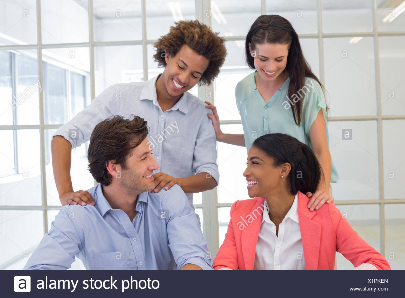 Coworkers congratulating and praising each other - Stock Image