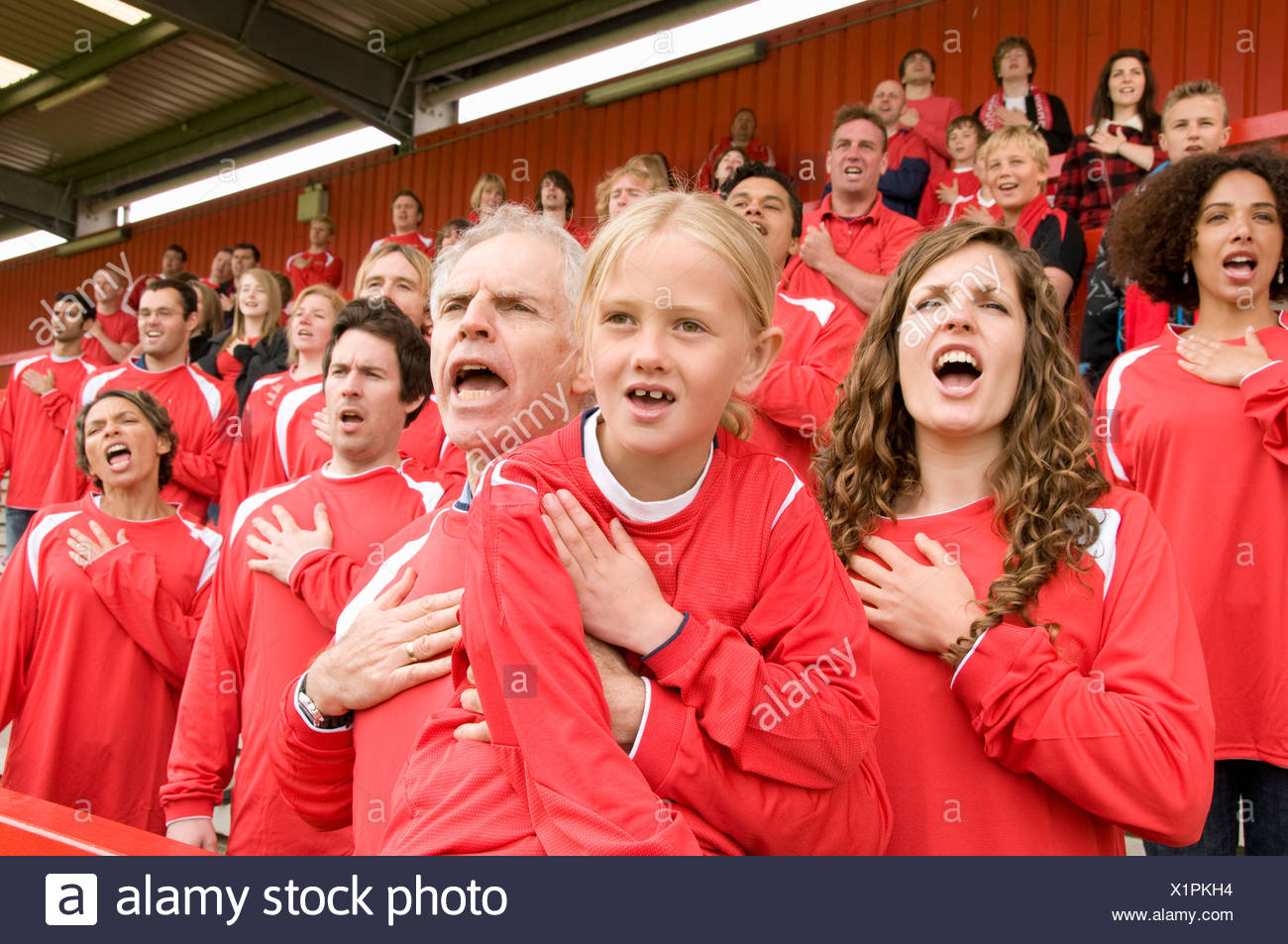 Fans singing anthem at football match Stock Photo