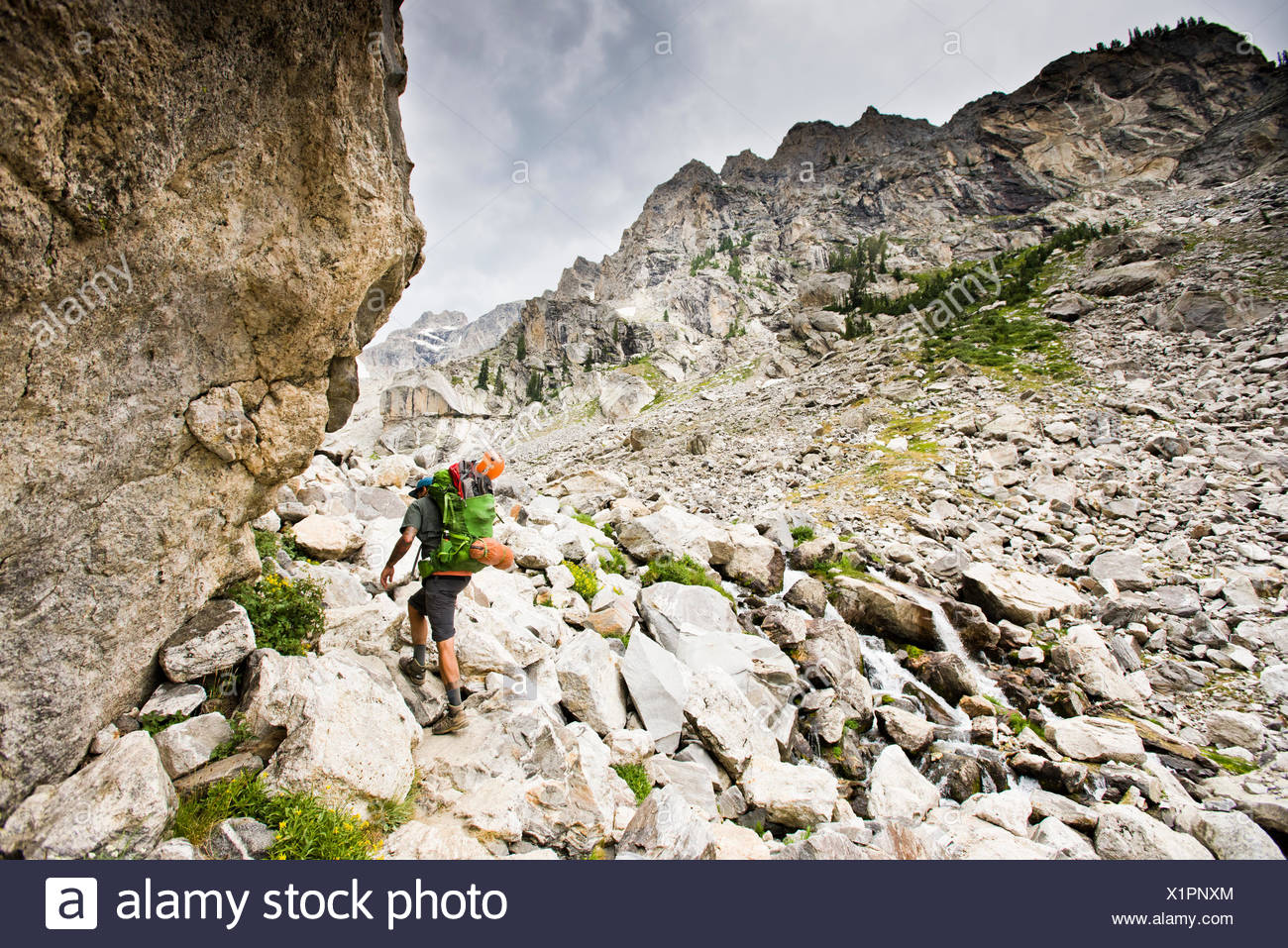 A backpacker going through rocky terrain. - Stock Image