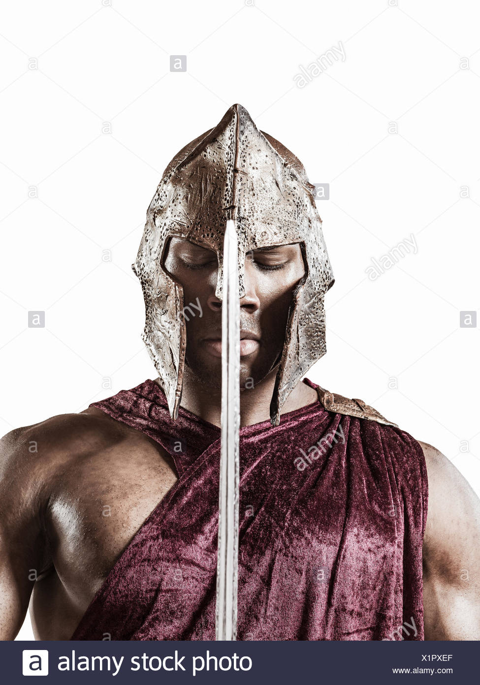 Studio portrait of poised young man dressed as gladiator with helmet and sword - Stock Image