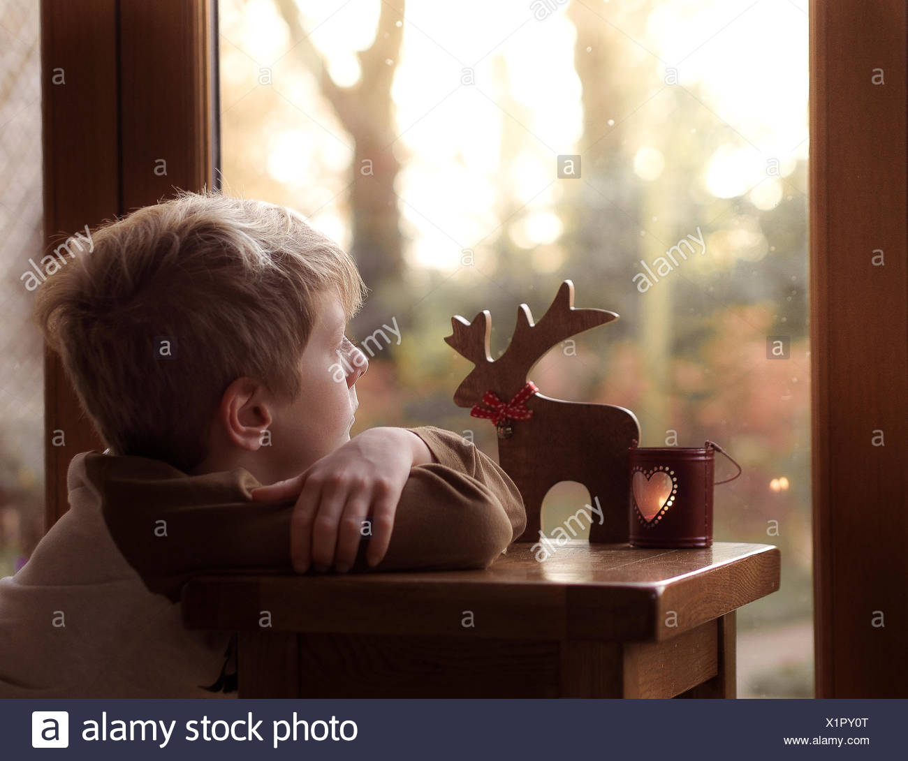 Boy (6-7) looking out of window - Stock Image