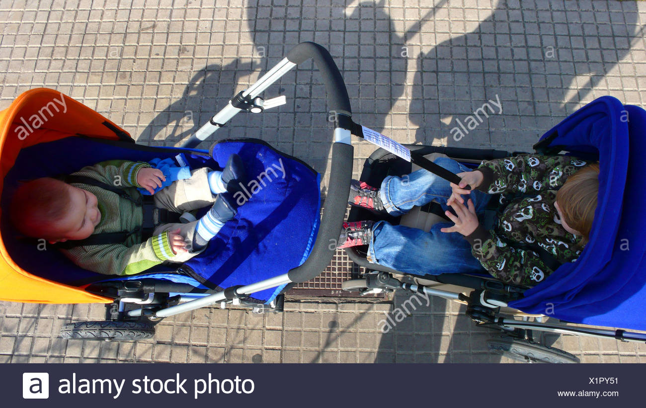 two little children standing vis-a-vis in their buggies - Stock Image