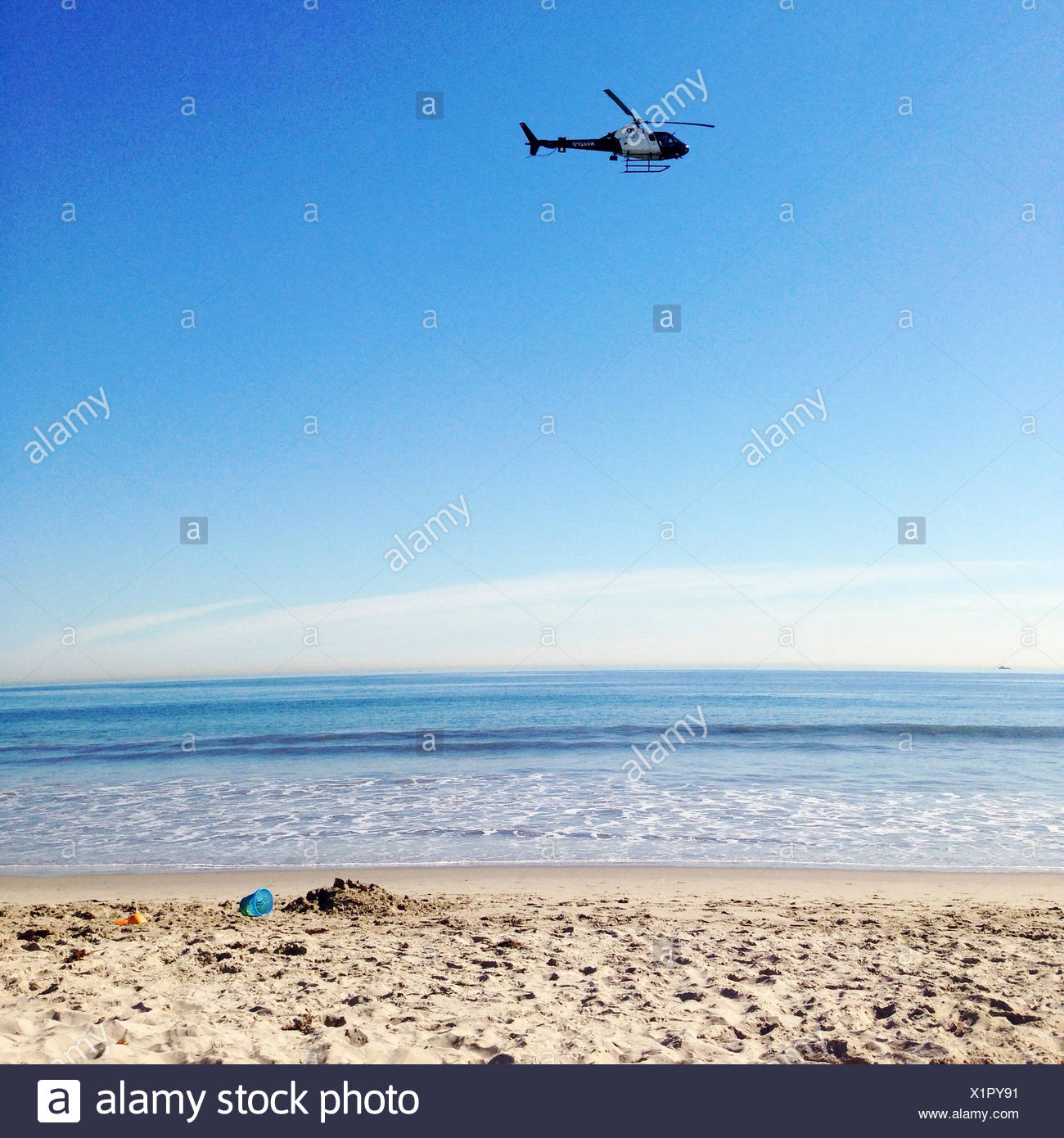 Helicopter flying over beach - Stock Image