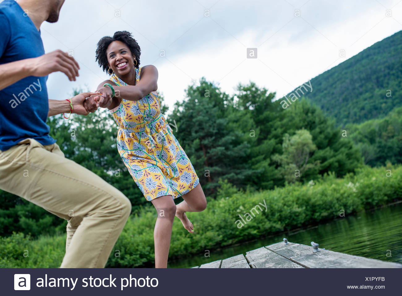 A couple trying to pull each other into the water off a jetty - Stock Image