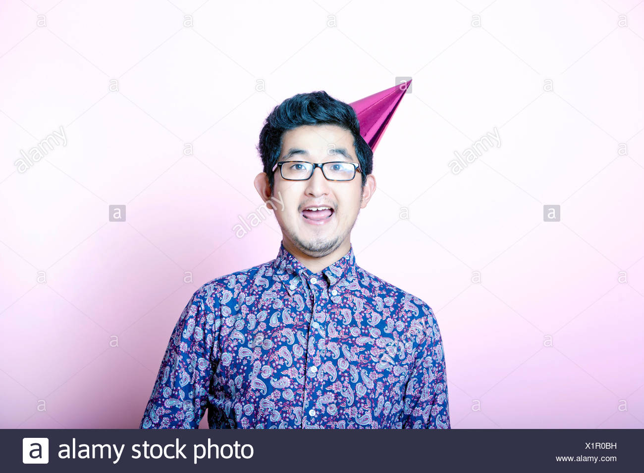 Young Geeky Asian Man wearing party hat - Stock Image