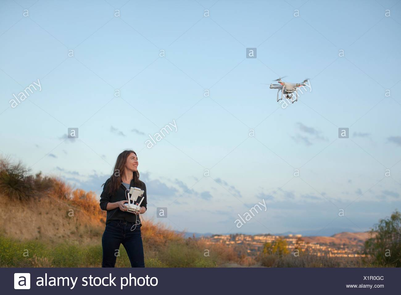 Female commercial operator flying drone looking up smiling