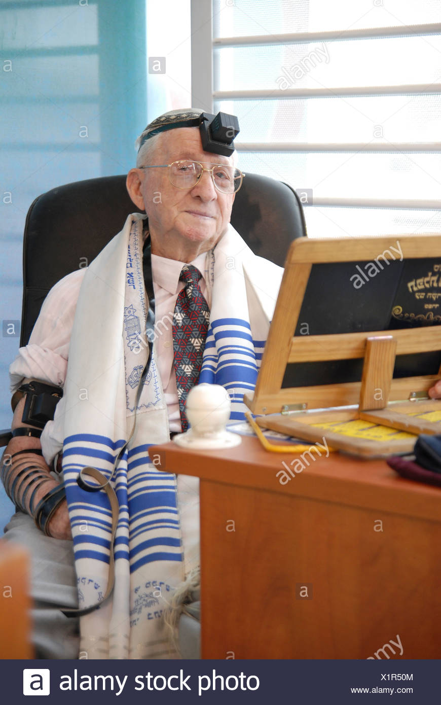 Mature man with Talis and tfillin in a synagogue - Stock Image