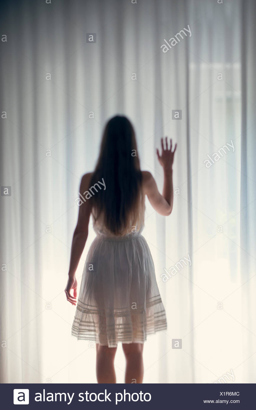 Mystical young woman standing in front of a white curtain, back view - Stock Image