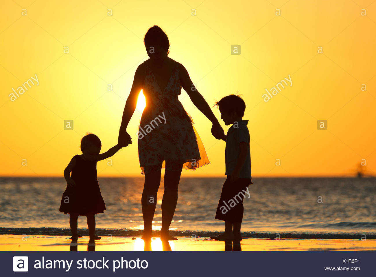 silhouettes of a mother and her two children on beach at sunset - Stock Image