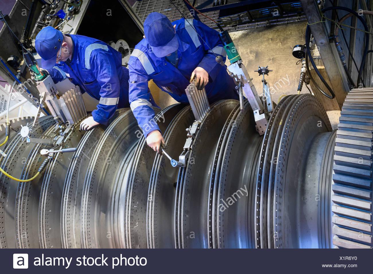 Engineers fitting blades to steam turbine in turbine repair bay - Stock Image