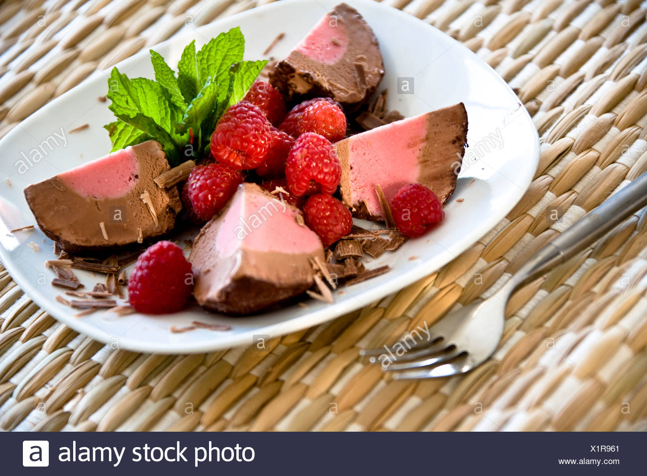 Chocolate Raspberry dessert, white plate and woven background - Stock Image