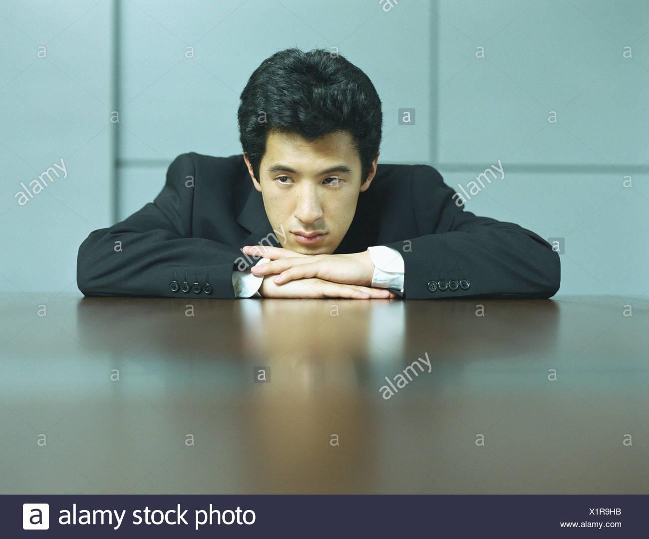Businessman resting head on hands, portrait - Stock Image