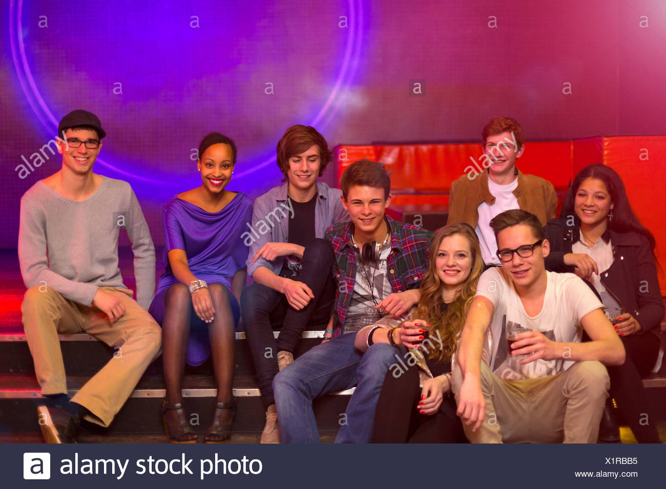Group of teenagers and young adults sitting on step at party holding drinks - Stock Image