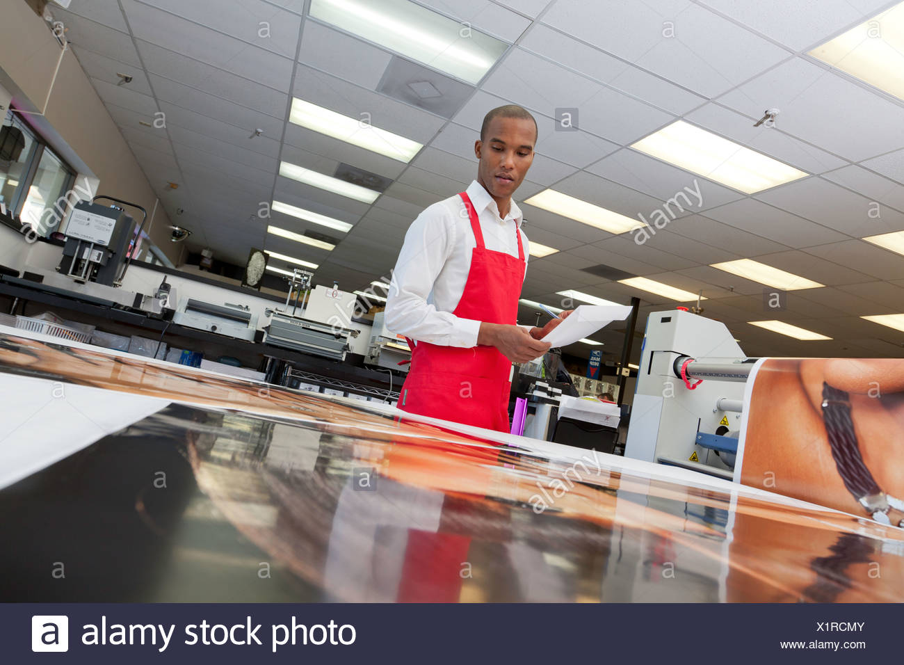Manual worker looking down at prints - Stock Image
