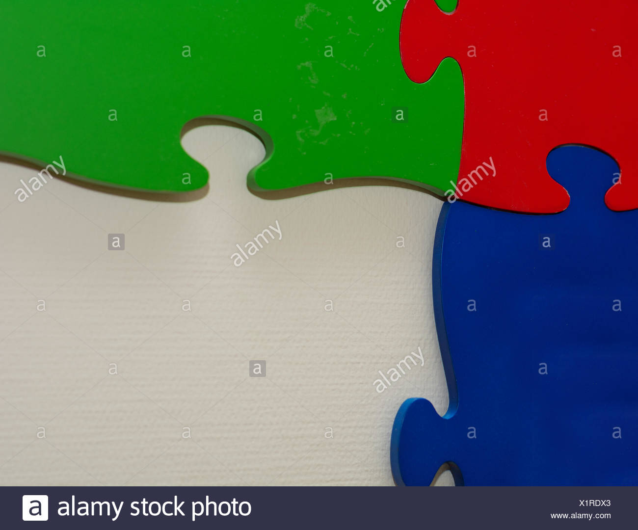 three giant puzzle pieces with intense colors - Stock Image