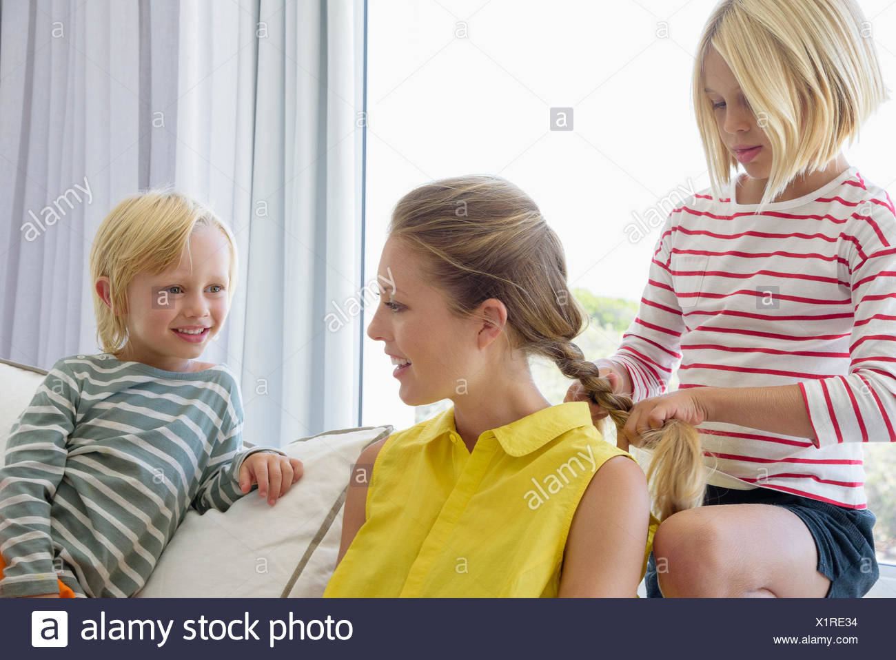 Happy mother and children sitting on couch in living room - Stock Image