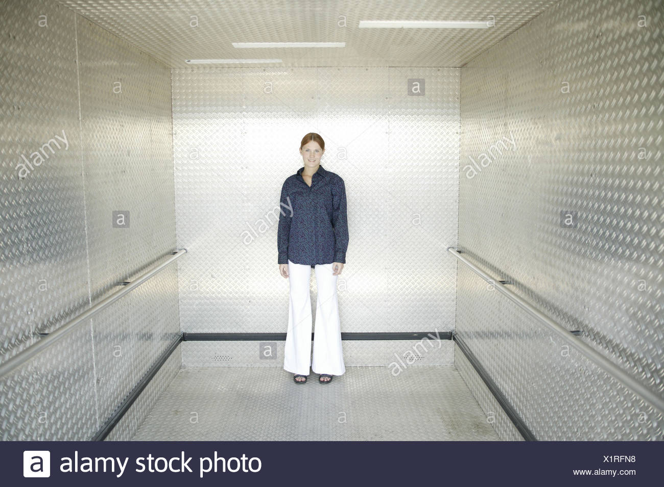 Lift, woman, young, friendly, 15 - 20 years, young persons, trainees, trainee, lift, lift, stand, course, openly, equalised, view camera, whole body, inside - Stock Image