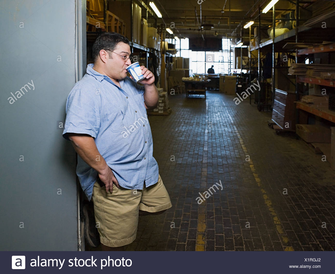 Manual worker drinking coffee - Stock Image