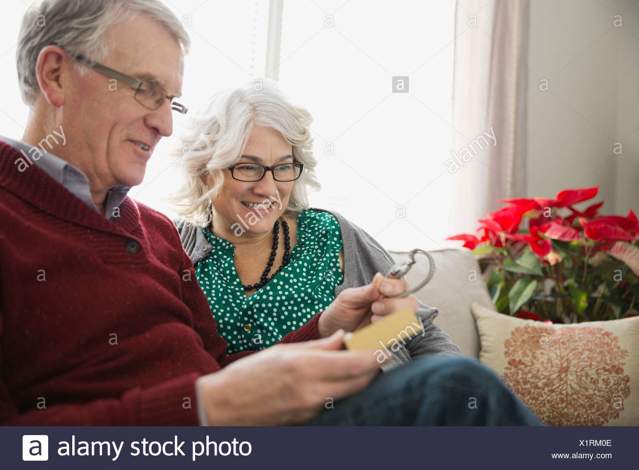 Senior man opening Christmas gift with wife - Stock Image