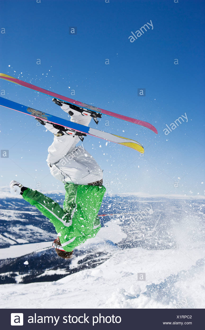 Man in green upside down & mid flight. - Stock Image