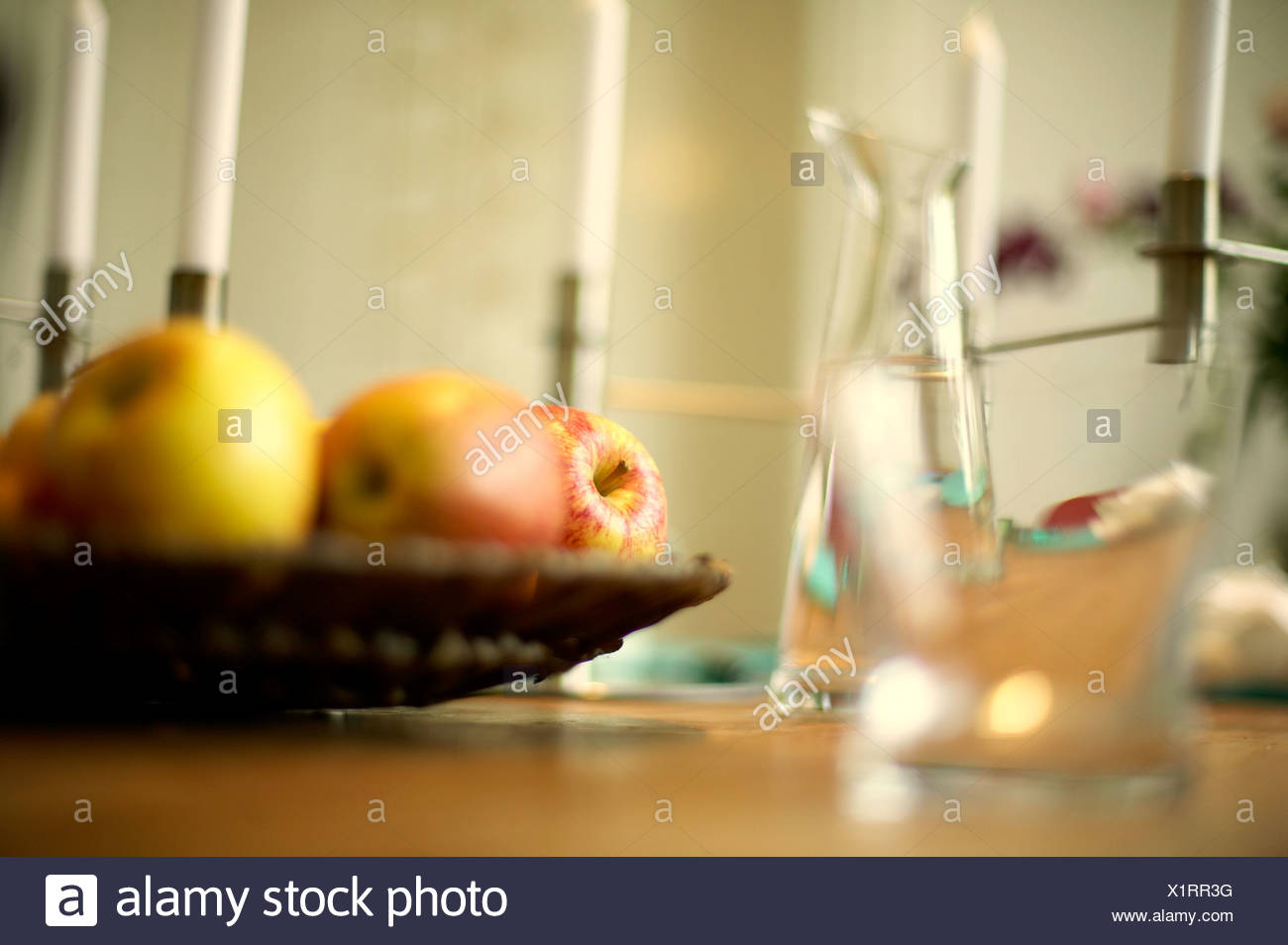Glasses and fruit bowl on a table - Stock Image