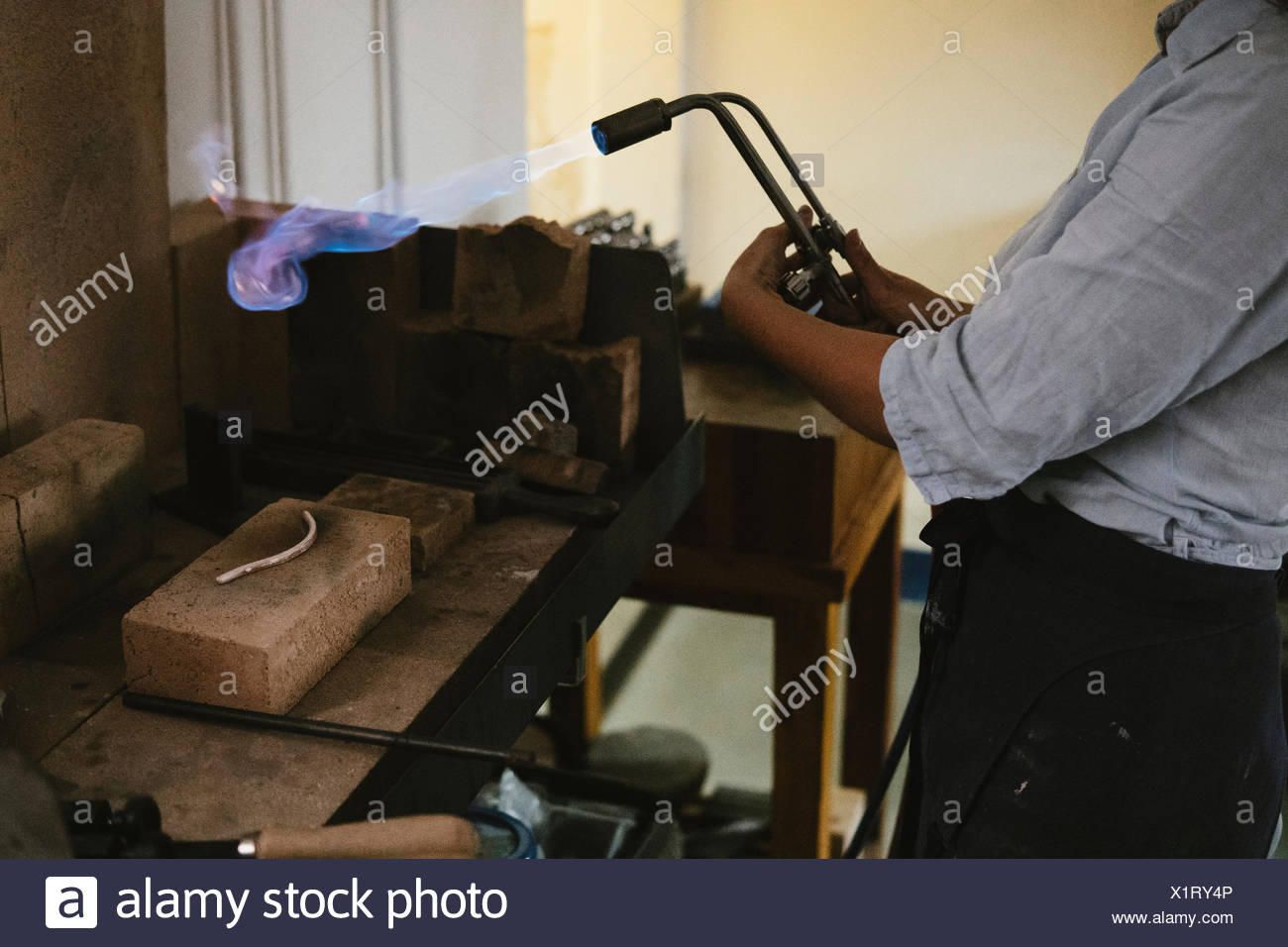 Mid section of female jeweller using flaming  blow torch at workbench Stock Photo
